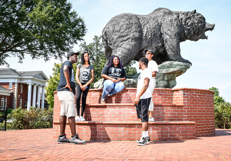 College students outside by bear statue.