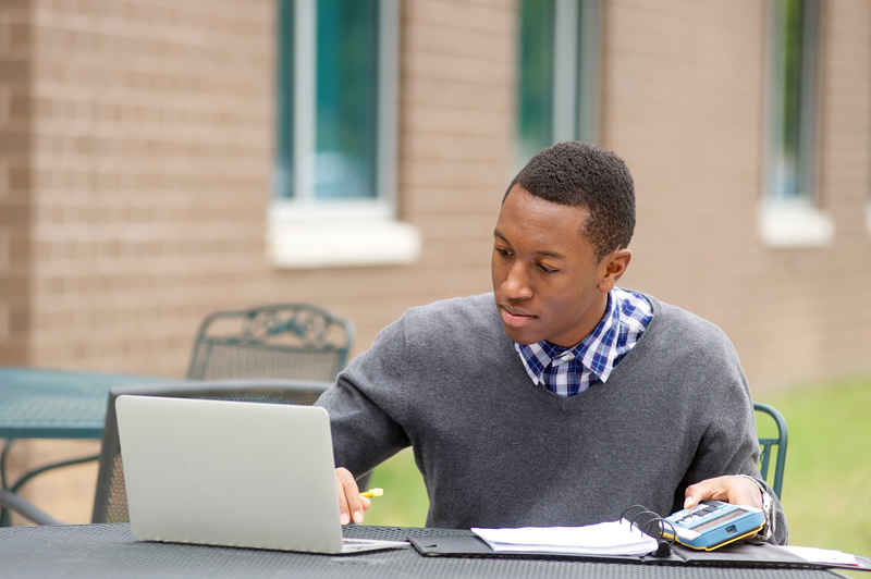 Man at outdoor table using laptop.