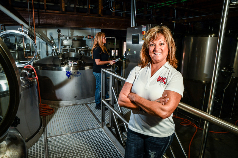 Woman behind the scenes at brewery.