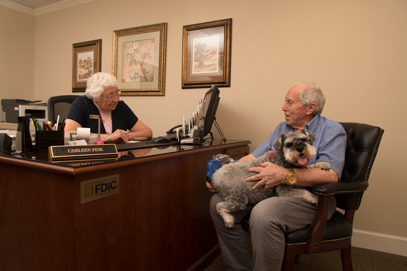 Senior man with dog meeting with mature woman in F&M Bank office.