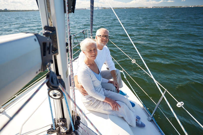 Mature couple on boat in open water.