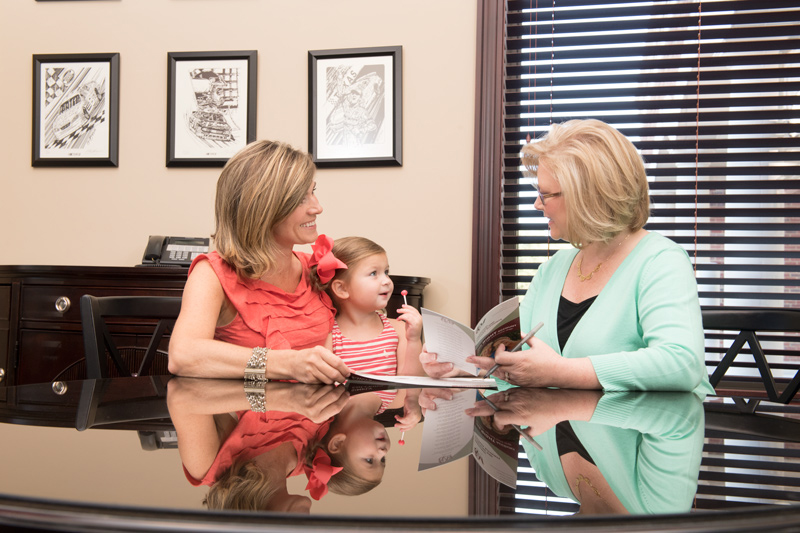 Mother and daughter meeting with woman in F&M bank office.